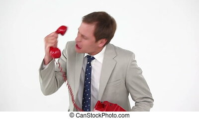 Angry man shouting in a red phone against white background