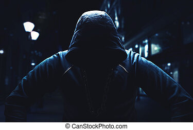 Angry man, sitting with a hood on in the street