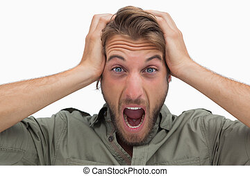 Angry man with hands on head on white background