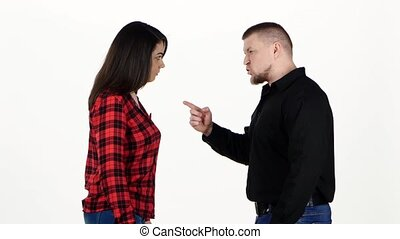 Angry man yelling at the woman and shakes her shoulders. White