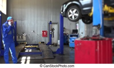angry mechanic talking with customer near lifted car in auto repair shop.