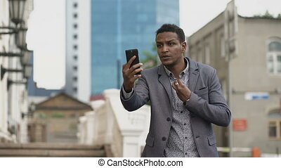 Angry Mixed race businessman having online video chat in business conference using smartphone