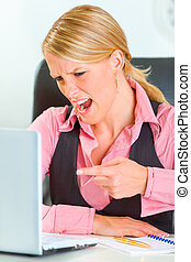 Angry modern business woman sitting at office desk and shouting on laptop