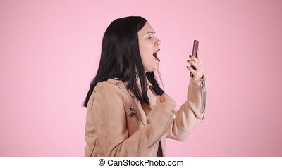 Angry modern businesswoman screaming down her mobile phone...