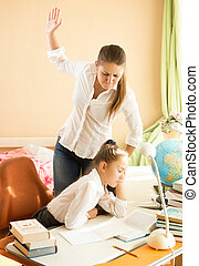 Angry mother giving a cuff on nape to daughter sleeping while doing homework