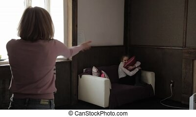 Angry mother scolding a disobedient child in living room at home. child is afraid