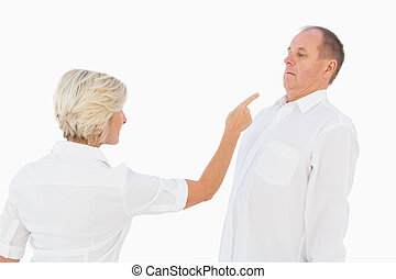 Angry older couple arguing with each other on white...