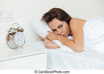 Angry pretty woman laying in bed in the morning and looking...