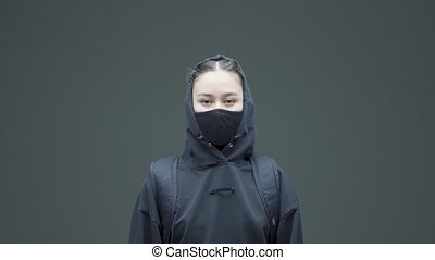 Angry rebel asian girl in black mask and hoodie protestor activist posing on gray studio background. High quality 4k footage
