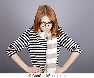 Angry red-haired girl in glasses and scarf.