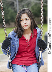 Angry, sad preteen girl sitting on swing