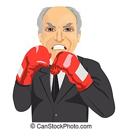 angry senior businessman with boxing gloves wearing gray suit