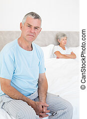 Angry senior man on bed with woman in background