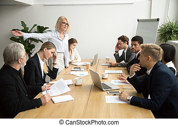 Angry senior woman boss firing employee at office team meeting