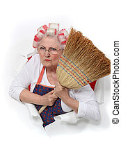 angry senior woman with curlers in her hair holding a broom