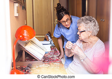 Angry Senior woman with her caregiver at home. Senior home care concept.
