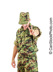angry soldier with hidden face in green camouflage uniform and h