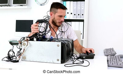 Angry technician pulling wires in broken computer in his...