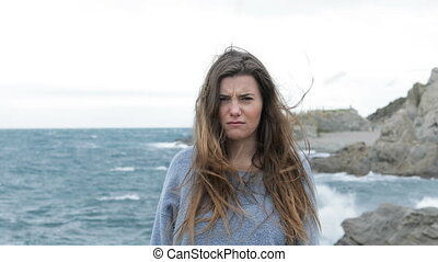 Angry teen looks at camera in a windy day - Angry teen walks...