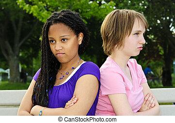 Angry teenage girls - Two unhappy teenage girls sitting on...