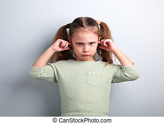 Angry unhappy kid girl coverd ears the fingers and gesturing that not want to listen on blue background with empty copy space