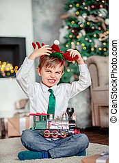 Angry upset little boy with a gift, toy train, under the Christmas tree on New Year's morning. Time to fulfill wishes.