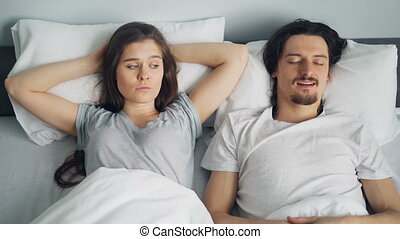 Angry wife covering face with pillow while sleeping husband snoring in bed