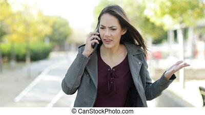 Angry woman arguing on phone in a park