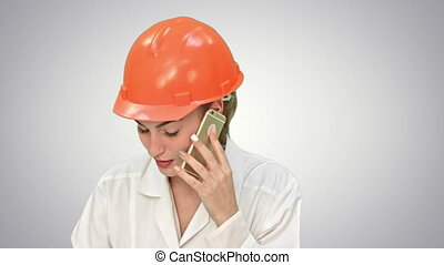 Angry woman construction worker in a hardhat shouting, talking on smartphone on white background.