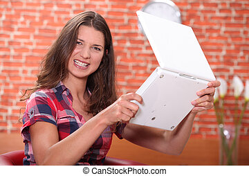 Angry woman holding a laptop