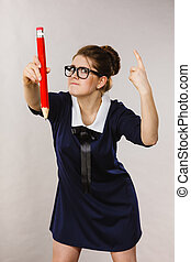 Angry woman holds big pencil in hand