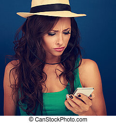 Angry woman in hat looking and reading sms on mobile phone in stress emotion on blue background. Closeup toned portrait