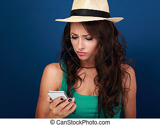 Angry woman in hat looking and reading sms on mobile phone in stress emotion on blue background. Closeup portrait