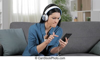 Angry woman listening to music using crashed phone sitting...
