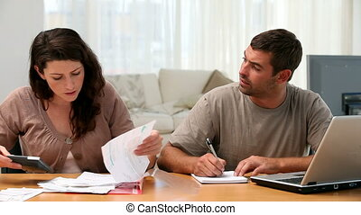 Angry woman looking at bills with her husband at a table in...