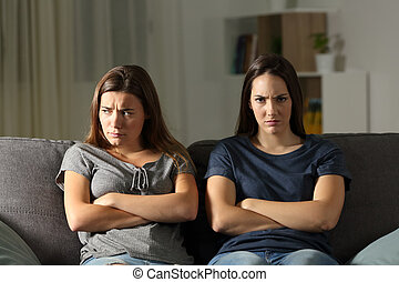 Angry woman looking at camera beside her friend