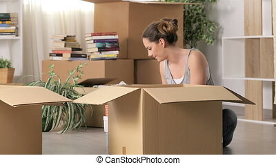 Angry woman moving home after divorce boxing belongings and...