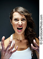 Angry woman on black background