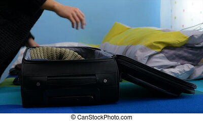 Angry woman packing up her clothes into a suitcase and leaving the house