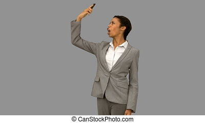 Angry woman raising her phone in the air on grey screen in...