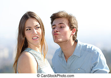 Angry woman rejecting a friend kiss
