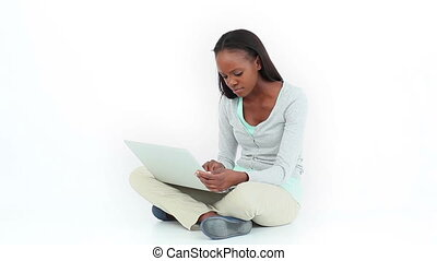 Angry woman typing on a computer against white background