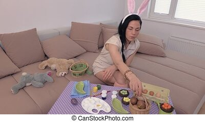 Angry woman with bunny ears near table with Easter eggs
