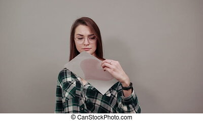 Young brunette girl blue green in checked shirt on grey background angry woman with glasses holding piece of paper with red heart, thumb turned down