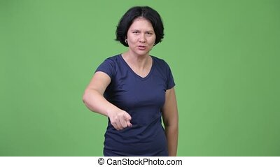 Angry woman with short hair talking to camera