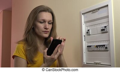 angry woman with smart phone call electrician services near circuit breaker