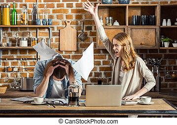 Angry woman yelling at upset man