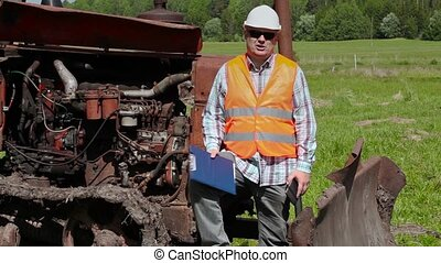 Angry worker talking near the bulldozer