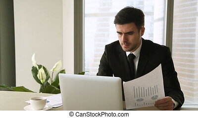 Angry worried businessman working on laptop, having problem with documents