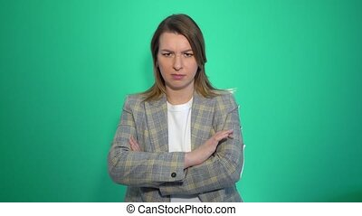 Angry young blonde girl standing with arms crossed over green background